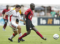 26 June 2004:   Dallas Burn Chris Gbandi dribbles the ball away from DC United Alecko Eskandarian at Cotton Bowl in Dallas, Texas.   DC United and Dallas Burn are tied 1-1 after the game.   Credit: Michael Pimentel / ISI
