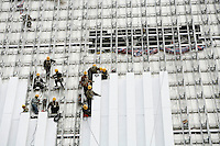 Workers install roof panels at the new China Central Television. China's CCTV and other important organisations and businesses are gobbling up space in the CBD. The area is being built at a break-neck pace in order to be complete and ready for the opening of the Beijing olympics in 2008..03 Apr 2007