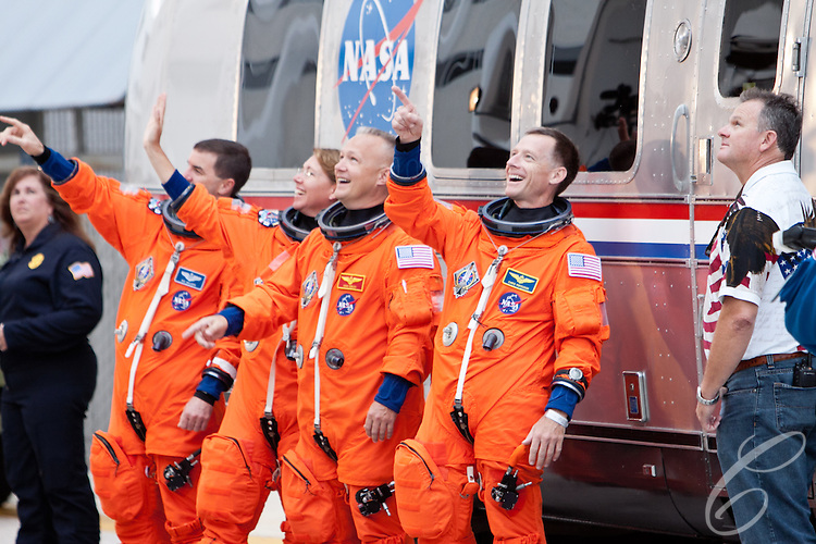 The crew of the Space Shuttle Atlantis acknowledge NASA employees gathered to watch the crew of the Space Shuttle Atlantis leave for the launch pad at Kennedy Space Center on Friday, July 8, 2011.  Atlantis' mission is the final one of the program's 30 year history.
