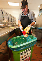 Marketplace staff cleans off plates into compost bins on July 15, 2011. (Photo by Marc Campos, Occidental College Photographer)