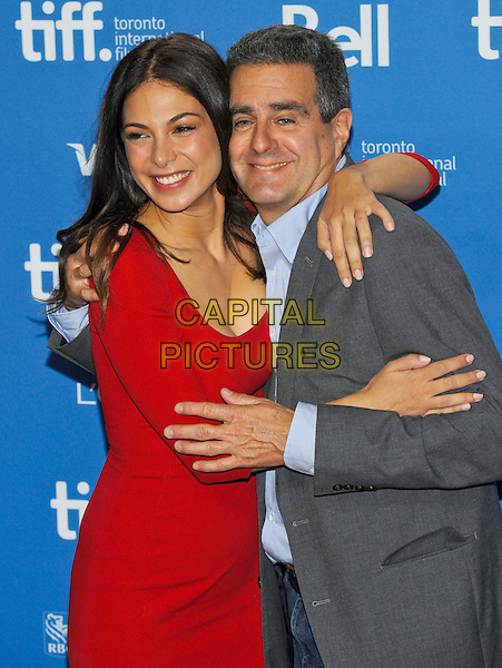 Moran Atias, Michael Nozik<br /> &quot;Third Person&quot; Press Conference  - 2013 Toronto International Film Festival held at TIFF Bell Lightbox, Toronto, Ontario, Canada.<br /> September 10th, 2013<br /> half length red dress grey gray suit jacket blue shirt hug embrace <br /> CAP/ADM/BPC<br /> &copy;Brent Perniac/AdMedia/Capital Pictures