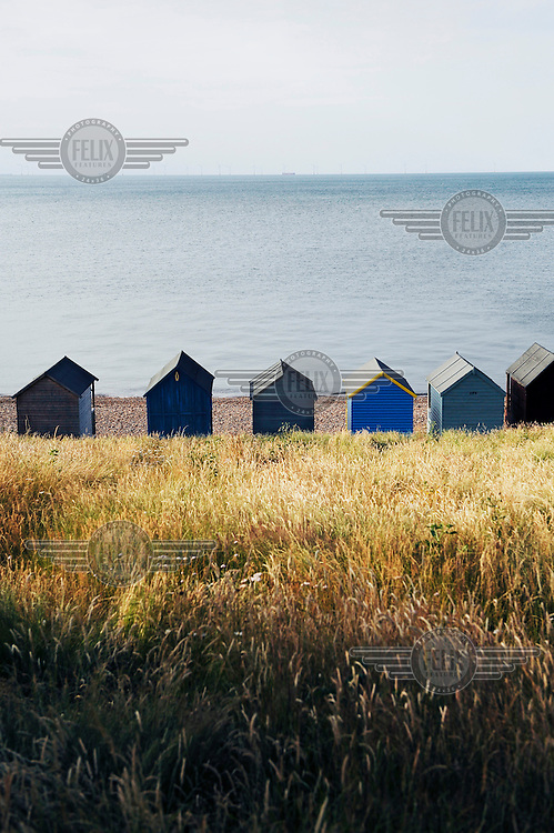 Beach houses by the sea side at Herne Bay in Kent. Wind turbines can be seen on the horizon.