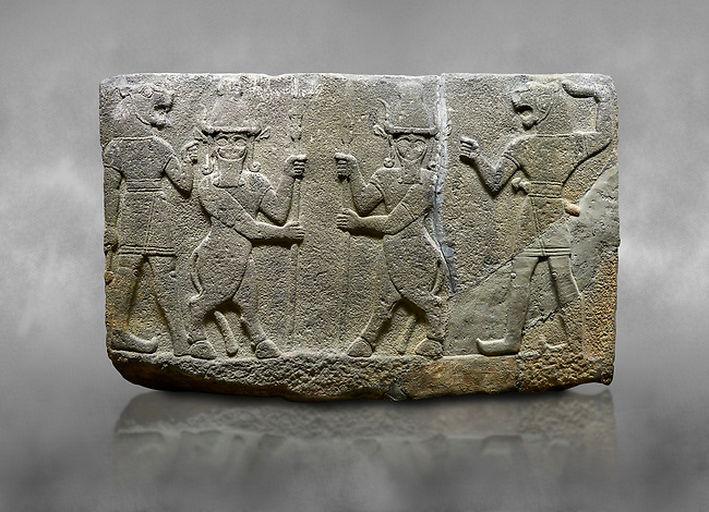 Hittite relief sculpted orthostat stone panel of Herald's Wall. Basalt, Karkamıs, (Kargamıs), Carchemish (Karkemish), 900-700 B.C. Anatolian Civilisations Museum, Ankara, Turkey.<br /> <br /> Protective mixed creatures. One each hand of the lion-headed men is in the form of a fist. The mace on the left is over the head of the weapon on the right. The two bull-men in the middle carry one spear each in their hands. Bull-man is known as Kusarikku, and the lion-man is known as Ugallu. <br /> <br /> Against a grey art background.