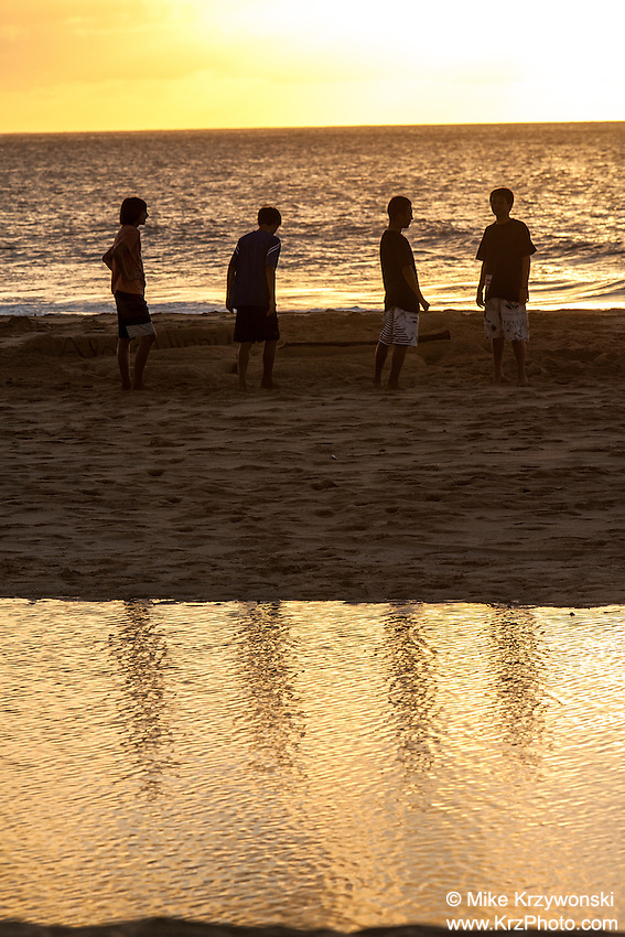 Four boys standing on the beach near tide pool at sunset on the North Shore, Oahu, Hawaii