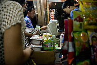 Shoppers check out at a cash register in a small food store in Qingdao, Shandong, China.