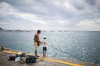 A father and son fish off the docks on Sunday, Sept. 20, 2015, in Positano, Italy. (Photo by James Brosher)