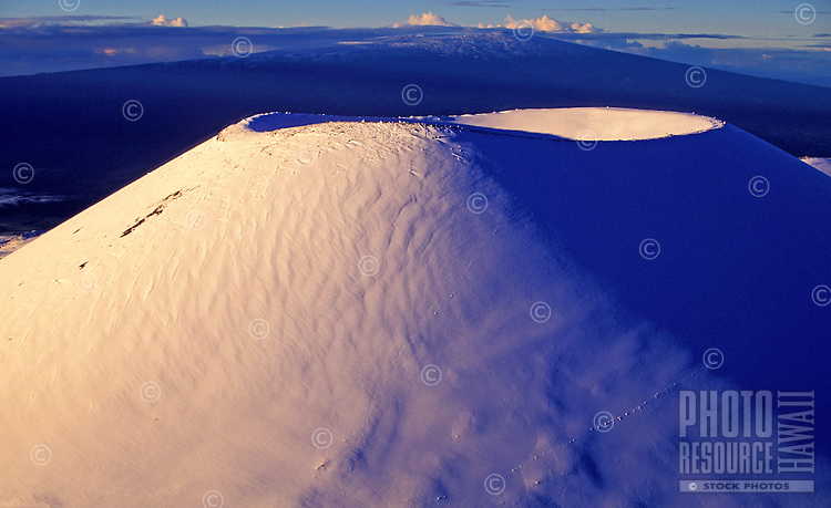 The snow topped cinder cone of the dormant volcano Mauna Kea rests majestically among the clouds.