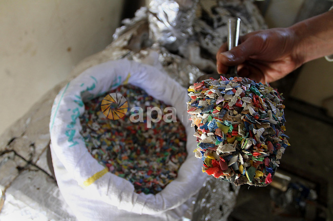 Palestinian Mahmoud Soboh, 28, displays grinded plastic at a workshop in his house in Nuseirat refugee camp, central Gaza Strip, April 9, 2014. Soboh succeeded in production of fuel oil by the thermal analysis of the plastic, which analysts say if carried out more broadly can ease the Egyptian-Israeli blockade on Gaza Strip which curbs imports of fuel and building supplies. Photo by Mohammed Asad