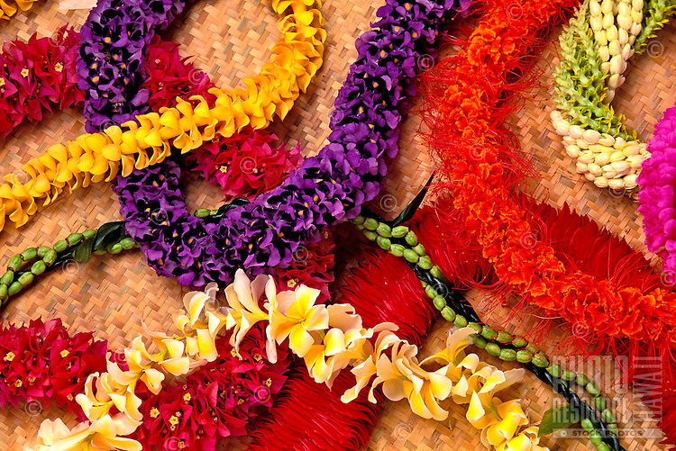 An assortment of beautiful floral leis are arranged  on a woven lauhala mat. Types include bougainvillea, red torch ginger, plumeria, puakenikeni, Ola'a beauty, ohai ali'i, pikake, and pakalana with ti leaf.