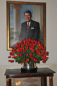 "Washington, DC - December 3, 2008 -- Tulips decorate a table underneath the portrait of former United States President Ronald Reagan during a media preview of the 2008 holiday decorations and tasting event on the State Floor of the White House in Washington, D.C. on Wednesday, December 3, 2008.  The theme of this years decorations is ""a Red, White, and Blue Christmas""..Credit: Ron Sachs / CNP"