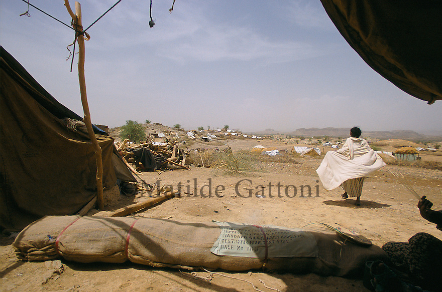 Eritrea - Debub- Woman walking away from her family tent in an IDP camp. As a result of 30 years of war for independence against Ethiopia (from 1961 to 1991) and another 3 years from 1997 to 2000, there are 50,000 Eritreans currently living in internally displaced (IDP) camps throughout the country. These IDPs have fled three times in the last 10 years, each time because of renewed military conflict. They lived in relatives' homes when lucky enough, but mostly, the fled to the mountains, where they attempted to do what Eritreans do best, survive. Currently there is no Ethiopian occupation in Eritrea, but landmines prevent the IDPs from finally going home. .It is estimated that every Eritrean family lost two or three members to the war which makes the reality of the current emergency situation even more painful for Eritreans worldwide. Currently, the male population has been decreased dramatically, affecting the most fundamental socio-economic systems in the country. Among the refugee population, an overwhelming majority of families are female-headed, severely affecting agricultural production. For, IDPs in particular, 80% of households are female-headed..The unresolved border dispute with Ethiopia remains the most important drawback to Eritrea's socio-economic development, as national resources (human and material) continue to be prioritized for national defense. Eritrea is vulnerable to recurrent droughts and variable weather conditions with potentially negative effects on the 80 percent of the population that depend on agriculture and pastoralism as main sources of livelihood. The situation has been exacerbated by the unresolved border dispute, resulting in economic stagnation, lack of food security and increased susceptibility of the population to various ailments including communicable diseases and malnutrition..
