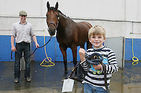 3/8/2010. James Ryan aged 5 from Oldtown Co Dublin is pictured at the RDS with PJ Casey getting his horse ready for the start of the Fáilte Ireland Dublin Horse show. Picture James Horan/Collins Photos