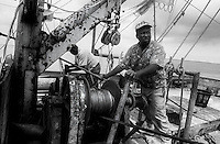 "Gene Orage works the winches that control the ""Rip Tide's"" shrimp nets. Shrimp prices are falling as more farm-raised shrimp are imported into the United States. As a result, domestic shrimpers must catch a few hundred pounds of shrimp just to cover their fuel costs."