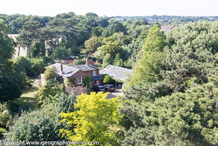 Historic old vicarage building set amongst trees in summer at Bawdsey, Suffolk, England, UK view from church tower