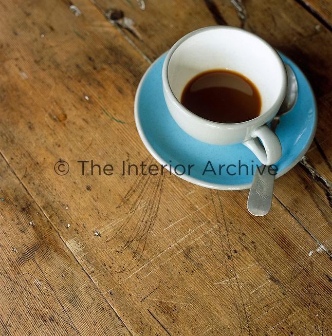 The remains of a cup of coffee on a worn wooden table