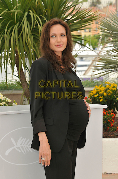"""ANGELINA JOLIE .""""The Exchange"""" ( formerly titled """"Changeling"""" ) photocall at Palais de Festival during the 61st Cannes International Film Festival, Cannes, France. .20th May 2008 .half length black jacket hand on stomach belly pregnant top.CAP/PL.©Phil Loftus/Capital Pictures."""