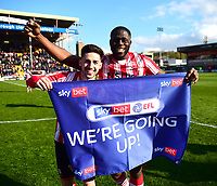 Lincoln City's Tom Pett, left, and John Akinde celebrate promotion<br /> <br /> Photographer Andrew Vaughan/CameraSport<br /> <br /> The EFL Sky Bet League Two - Lincoln City v Cheltenham Town - Saturday 13th April 2019 - Sincil Bank - Lincoln<br /> <br /> World Copyright &copy; 2019 CameraSport. All rights reserved. 43 Linden Ave. Countesthorpe. Leicester. England. LE8 5PG - Tel: +44 (0) 116 277 4147 - admin@camerasport.com - www.camerasport.com