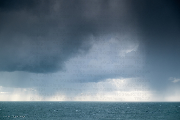 Rain clouds at the sea on the horizon