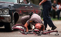 Florida Highway Patrol trooper Gary Carnley investigates the scene where a bike and car came to rest after hitting a young boy and killing him on Kirk Street.