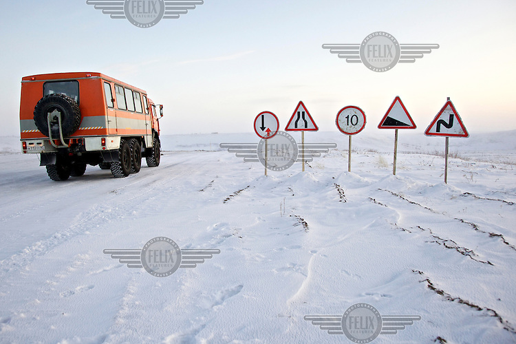 A vehicle passes by a group of roadsigns on an ice-road built to serve gas and oil companies exploring in the Nenets Autonomous Region in the Russian Arctic. In the summer the road will melt away revealing the marshland that lies beneath. /Felix Features