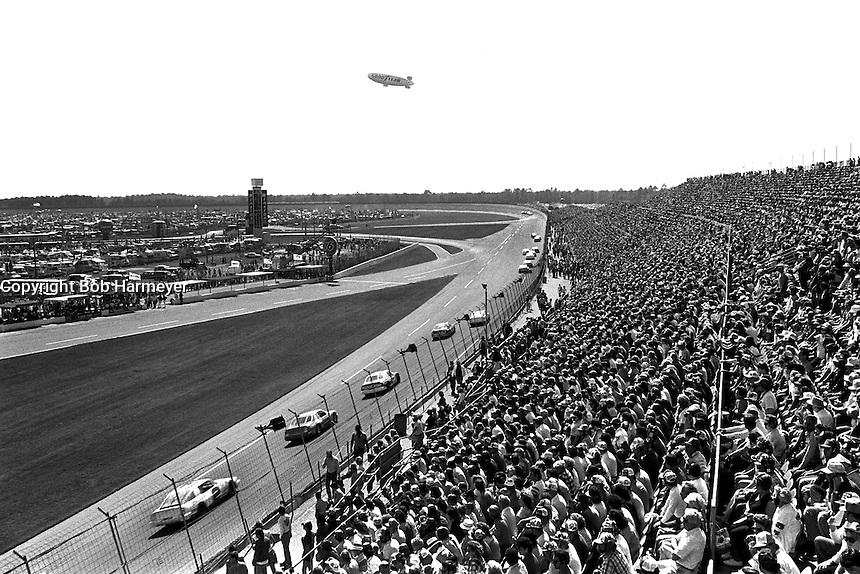 DAYTONA BEACH, FL - FEBRUARY 16: With a Goodyear Blimp overhead, a group of cars race toward Turn 1 during the Daytona 500 NASCAR Winston Cup race at the Daytona International Speedway in Daytona Beach, Florida, on February 16, 1986.