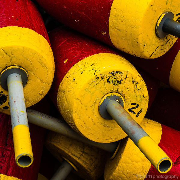 Red and yellow fishing buoys stacked on dock