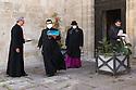 12 aprile 2020, Sassari, piazza Duomo. Pasqua di Resurrezione. L'Arcivescovo di Sassari, Monsignor Gianfranco Saba, torna all'Arcivescovado dopo la celebrazione della messa. Lo accompagna un sacerdote che porta con se un Tiramisù, ricevuto in dono da una fedele.