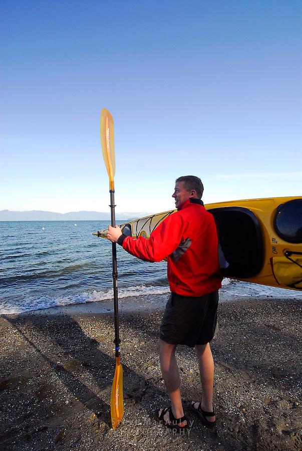 Male paddler in yellow kayak and red paddling jacket holding kayak on shoulder, Sea Kayaking the San Juan Islands, WA.