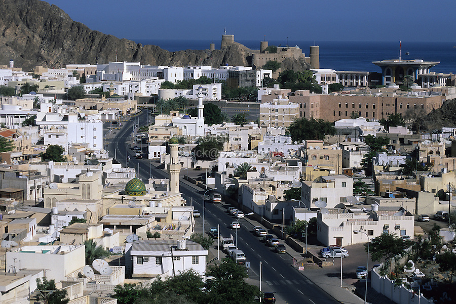 Muscat, Oman.  Fort Mirani, built by the Portuguese in the 16th. century, overlooks the city, whose rooftops are dotted with satellite dishes linking Oman to a 21st. century global communications network.  The sultan's palace, Al-Alam, is on the right.  Surrounding the town, and visible on the left, are chocolate-brown ophiolites, a metamorphic, igneous rock.
