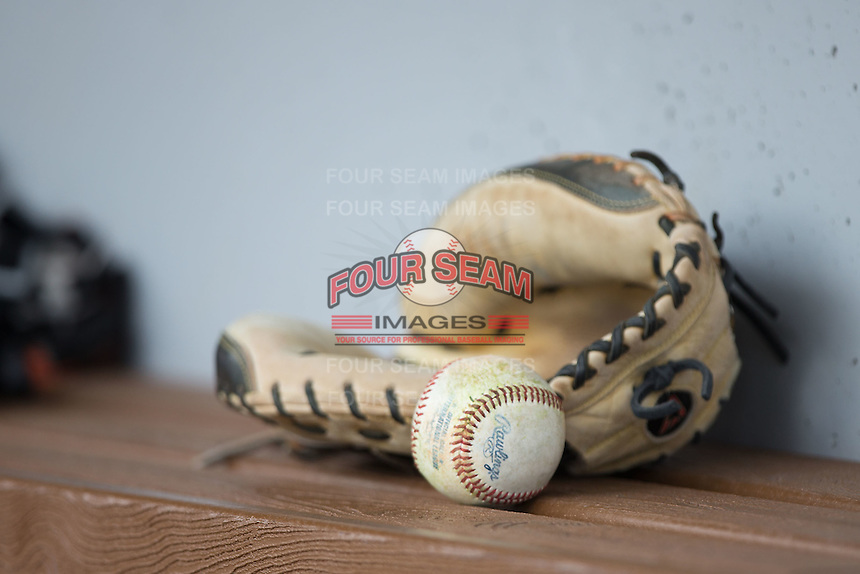 A baseball and catcher's mitt sit on the bench in the visitor's dugout during the International League game between the Norfolk Tides and the Charlotte Knights at BB&T BallPark on June 7, 2015 in Charlotte, North Carolina.  The Tides defeated the Knights 4-1.  (Brian Westerholt/Four Seam Images)