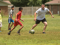 NWA Democrat-Gazette/ANTHONY REYES • @NWATONYR<br /> Juan Barroso, 11, pushes the ball up the pitch as Philip Group, with the Springdale police department, defends Wednesday June 24, 2015 during a soccer game at Jones Elementary School in Springdale. Group and other officers were at the school as part of the Sandlot Program where they help mentor the students through play. The officers open up the gymnasium to the children who play and can eat lunch at the school free of charge.