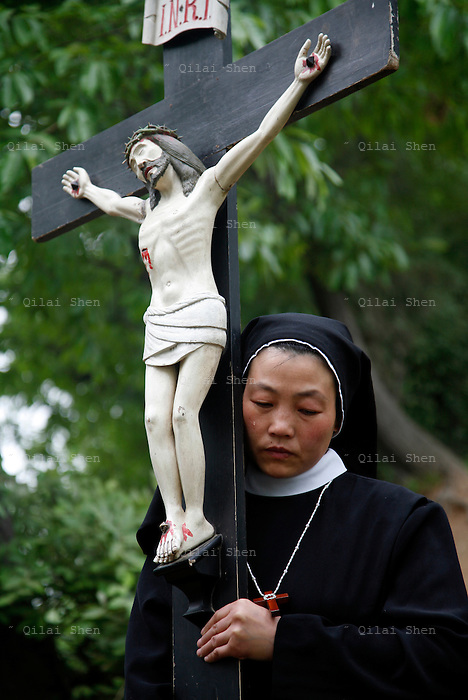 An teary Catholic nun from Tianshui, Gansu Province, carries a cross while praying on Shizishan (Cross Mountain) near Meixian, Shaanxi Province, China on Thursday, 03 May 2007. Also known as the oriental Mount Calvary, Shizishan see pilgrims from all over northwestern China every 3rd of May to commemorate the suffering of Jesus Christ.