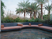 The open banquette area is used for evening entertainment.  The cushions are covered in outdoor fabric from Pierre Frey.   The gardens are planted with palm trees