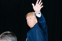 Republican presidential candidate and real estate mogul Donald Trump waves after speaking at a meeting of the New England Police Benevolent Association executive council at the Sheraton Portsmouth Harborside Hotel in Portsmouth, New Hampshire, USA. At the gathering, the group endorsed Trump for president. A small group of perhaps 20 Trump supporters stood outside the hotel and there was a larger group of anti-Trump protesters, mostly across the street. One of the protest organizers estimated that there were around 230 protesters gathered.Many protesters expressed disagreement with Trump's recent statements that he would ban all Muslims from entering the country. Trump brought up the recent shooting in San Berdardino, Calif., at the meeting.