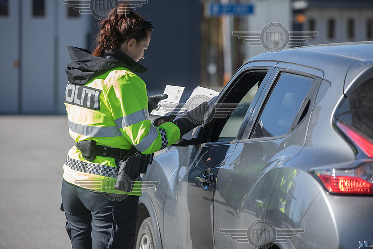 A woman showing her travel permits to a police officer.  Norwegian authorites introduced strict measures to combat the Coronavirus (COVID-19) in March 2020. This included closing the borders, and any Norwegians returning from abroad is given two weeks quarantine. <br /> <br /> Police and soldiers from the Home Guard of the Army (Heimevernet) man checkpoints along side roads and regular border crossings to enforce the travel restrictions.<br /> <br /> <br /> <br /> ©Fredrik Naumann/Felix Features