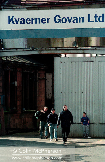 Three workers watched by a young boy leaving the Govan shipyard on the banks of the river Clyde in Glasgow at the end of their shift. At the time of this photograph, the shipyard was owned by Norwegian company Kvaerner, which sold it in 1999 to the newly-formed British firm BAE Systems. The yard subsequently depended entirely on orders from the Royal Navy to sustain its business and was periodically under threat of closing.