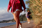 Seattle, Lincoln Park, Puget Sound, Woman in shorts walking along seawall in slight blur motion, Pacific Northwest,.