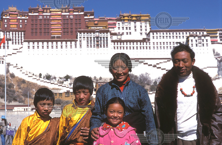 © Dermot Tatlow / Panos Pictures..Lhasa, TIBET..A Tibetan family pose for a snap in front of the Potala Palace to celebrate Tibetan New Year.