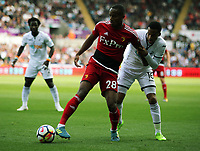 (L-R) Andre Carrillo of Watford challenged by Matrin Olsson of Swansea City during the Premier League match between Swansea City and Watford at The Liberty Stadium, Swansea, Wales, UK. Saturday 23 September 2017