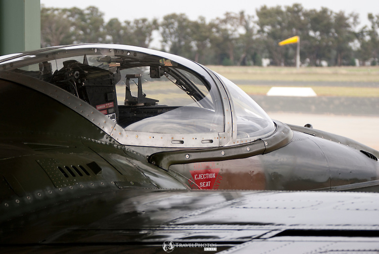 A Cessna A37B Dragonfly parked under cover in front of a hanger on a rainy day at the Temora Aviation Museum