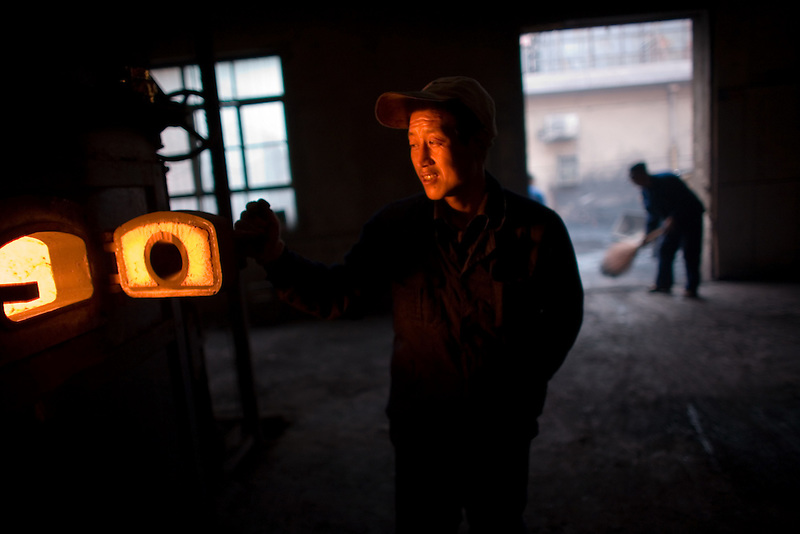 A worker checks burning coal in a large furnace, which is used for heating an entire neighborhood in Linfen.