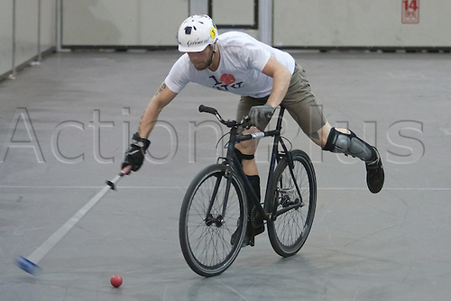 15.01.12 London, England. Player shoots for goal during the London International Invitational bike polo quarter finals match at The Bike Show between Hooks (beige shirts) from Paris, France and Edisons (white shirts) from Germany at ExCeL Centre, East London.