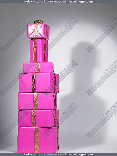 Pile of presents, pink stacked gift boxes in a shape of an alcohol bottle.