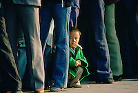 Small child crouching among adults queuing in Tiananmen Square to enter the Forbidden City, Beijing, China (Peking).