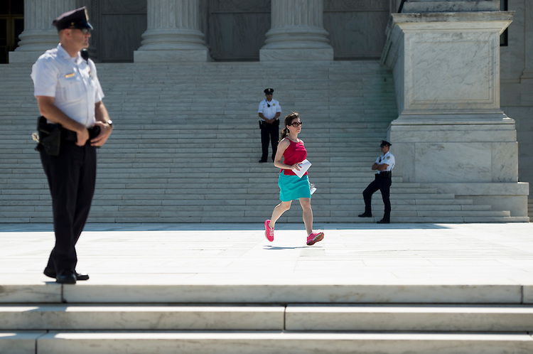 UNITED STATES - JUNE 22: A runner for one of the television news networks races with papers to the camera positions outside of the Supreme Court in Washington on Monday, June 22, 2015. (Photo By Bill Clark/CQ Roll Call)