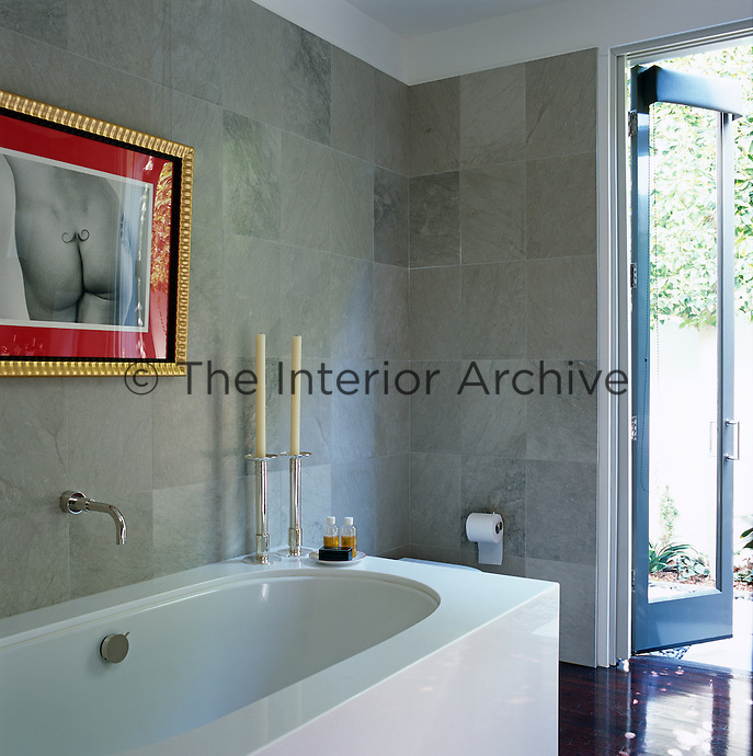 The walls of this contemporary bathroom are lined with tiles of a pale grey stone and the photograph is by Gig Stoel