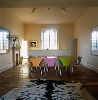 This former sitting room of a 19th century house is now a general family area for cooking and eating, with a long pine table and colourful Arne Jacobsen chairs
