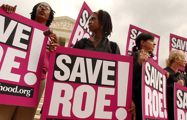 From left, Sonya Clay, Jamia Wilson, Justine Augeri, and members of Planned Parenthood, displayed signs and wore robes in front of the Supreme Court.  They were waiting for the resignation of Chief Justice William Rehnquist or Justice Sandra Day O'Conner, and wanted to remind paople of the importance of Roe v. Wade.