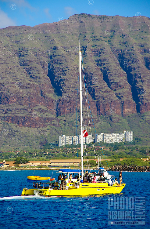 Sailboat with riders enjoy western shores of Oahu.
