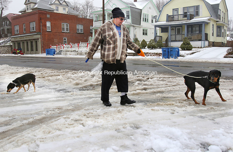 WATERBURY CT. 29 December 2015-122915SV05-Jaime Carrillo of Waterbury tries to make it through slushy ice while walking his dogs on East Main Street in Waterbury Tuesday. <br /> Steven Valenti Republican-American
